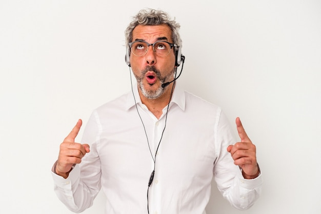 Middle age telemarketer caucasian man isolated on white background  pointing upside with opened mouth.