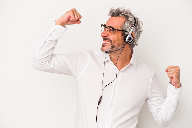 Middle age telemarketer caucasian man isolated on white background  raising fist after a victory, winner concept.