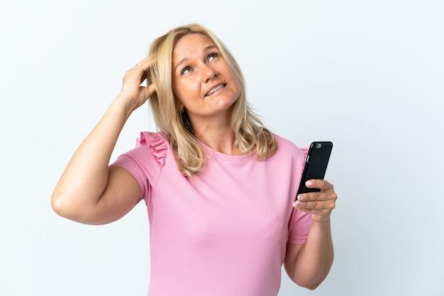 疑念と混乱した表情で白い壁に隔離された携帯電話を使用して中年