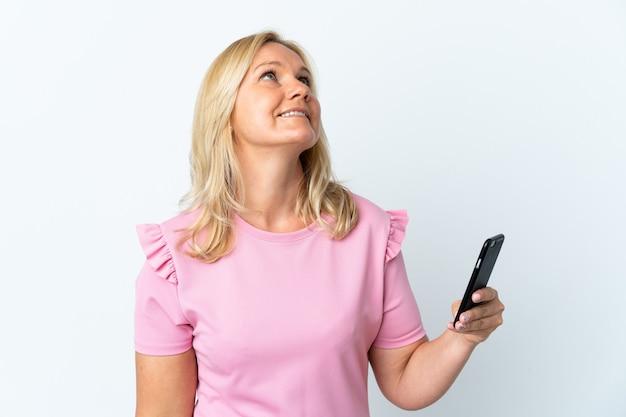 笑顔で見上げる白い壁に隔離された携帯電話を使用して中年