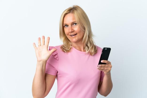 幸せな表情で手で敬礼する白い壁に分離された携帯電話を使用して中年