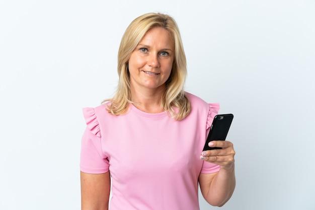 たくさん笑って白い壁に隔離された携帯電話を使用して中年