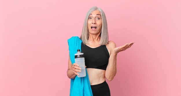 中年の白髪の女性は、タオルと水筒で信じられないほどの驚きに驚き、ショックを受け、驚きました。フィットネスコンセプト