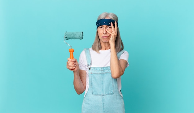 壁を塗るローラーで疲れた後、退屈、欲求不満、眠い中年の白髪の女性