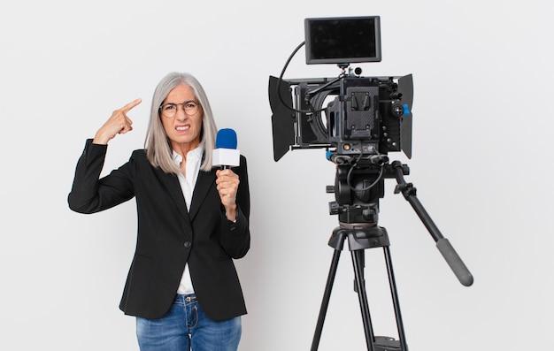 Женщина средних лет с белыми волосами чувствует себя смущенной и озадаченной, показывая, что вы сошли с ума и держите микрофон. концепция телеведущего