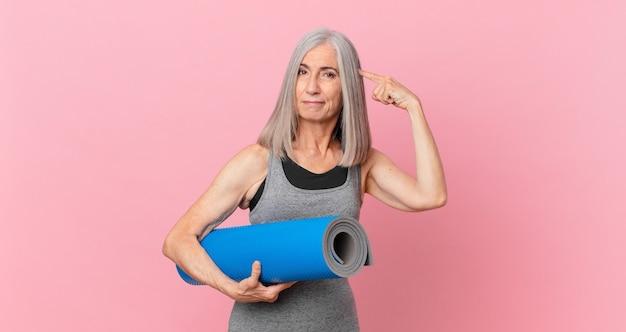 Женщина средних лет с белыми волосами, чувствуя себя смущенной и озадаченной, показывая, что вы безумен, и держит коврик для йоги. фитнес-концепция