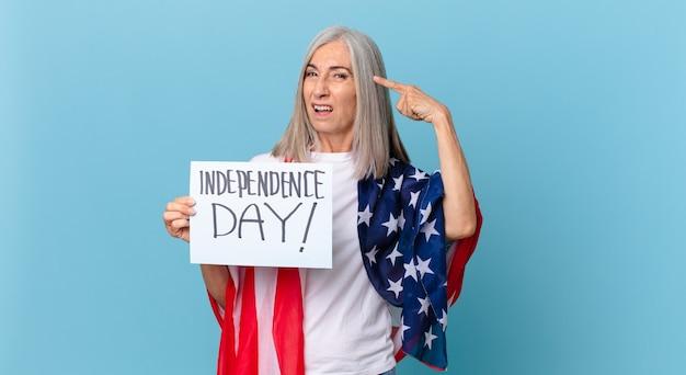 Женщина средних лет с белыми волосами чувствует смущение и недоумение, показывая, что вы сошли с ума. концепция дня независимости