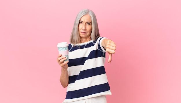 Женщина среднего возраста с белыми волосами чувствует себя крестно, показывает палец вниз и держит контейнер для кофе на вынос