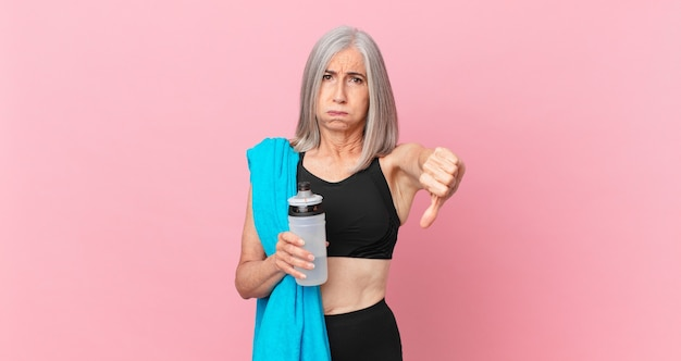 Middle age white hair woman feeling cross,showing thumbs down with a towel and water bottle. fitness concept