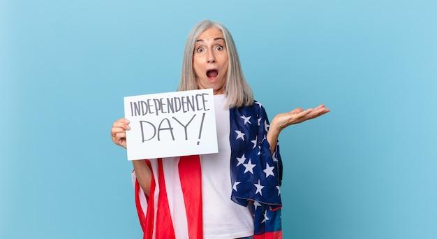 Женщина средних лет с белыми волосами, чувствуя себя чрезвычайно шокированной и удивленной. концепция дня независимости