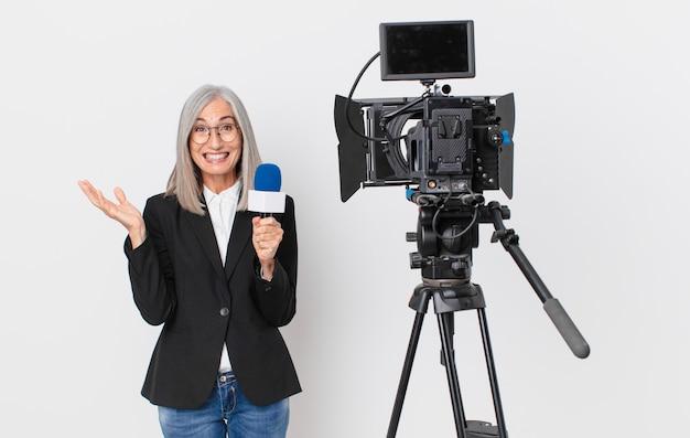 Женщина средних лет с белыми волосами чувствует себя счастливой и удивленной чему-то невероятным и держит микрофон. концепция телеведущего