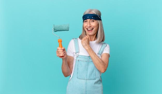 Женщина среднего возраста с белыми волосами чувствует себя счастливой и сталкивается с проблемой или празднует с роликом, раскрашивающим стену