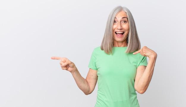 幸せを感じ、興奮して横を向いて自分を指している中年の白髪の女性
