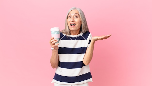 Middle age white hair woman feeling happy and astonished at something unbelievable and holding a take away coffee container
