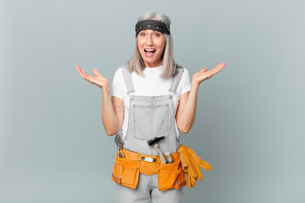 Middle age white hair woman feeling happy and astonished at something unbelievable and wearing work wear and tools. housekeeping concept