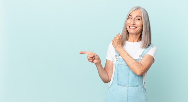 Middle age white hair woman feeling happy and facing a challenge or celebrating and pointing to the side