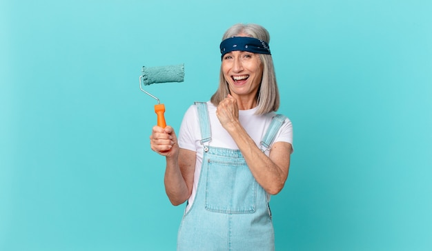 Middle age white hair woman feeling happy and facing a challenge or celebrating with a roller painting a wall