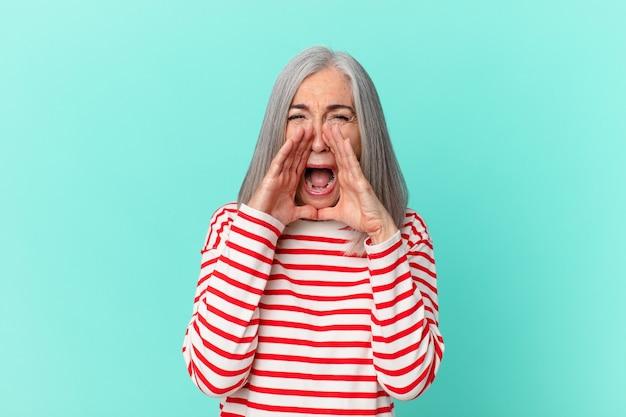 幸せを感じて、口の横に手で大きな叫びを与える中年の白髪の女性