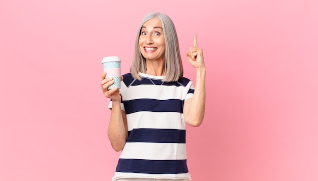 Middle age white hair woman feeling like a happy and excited genius after realizing an idea and holding a take away coffee container