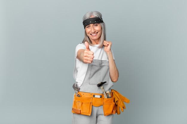 중년의 백발 여성은 자부심을 느끼고 엄지손가락을 치켜들고 긍정적으로 웃고 작업복과 도구를 착용합니다. 가사 개념
