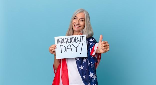 Женщина средних лет с белыми волосами чувствует себя гордой, позитивно улыбаясь, с пальцами вверх. концепция дня независимости