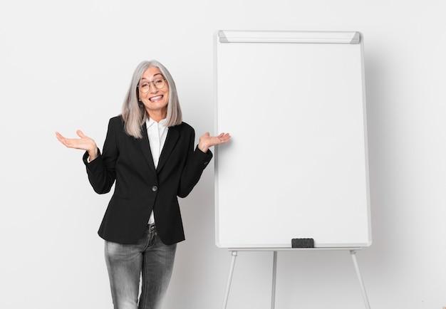 戸惑い、戸惑い、疑念を抱く中年白髪の女性とボードコピースペース。ビジネスコンセプト
