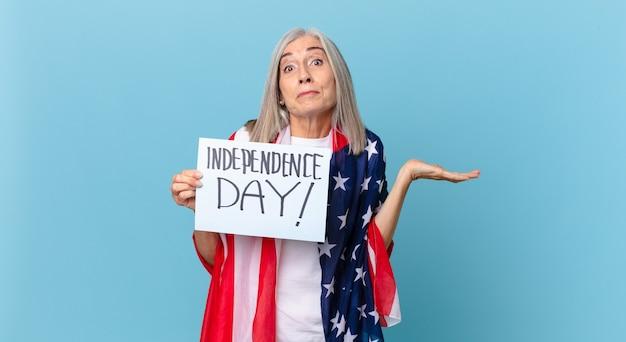 中年の白髪の女性は困惑し、混乱し、疑っています。独立記念日のコンセプト