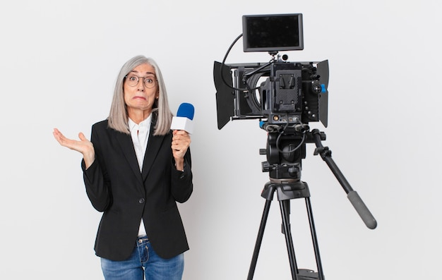 Middle age white hair woman feeling puzzled and confused and doubting and holding a microphone. television presenter concept