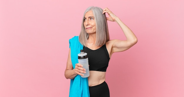 Middle age white hair woman feeling puzzled and confused, scratching head with a towel and water bottle. fitness concept