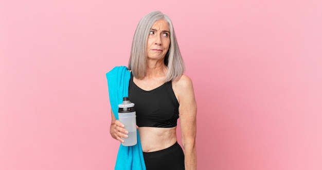 Middle age white hair woman feeling sad, upset or angry and looking to the side with a towel and water bottle. fitness concept
