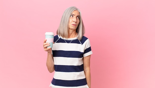 Женщина средних лет с белыми волосами чувствует себя грустной, расстроенной или злой, смотрит в сторону и держит контейнер для кофе на вынос