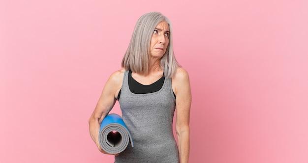 Женщина средних лет с белыми волосами чувствует себя грустной, расстроенной или сердитой, смотрит в сторону и держит коврик для йоги. фитнес-концепция