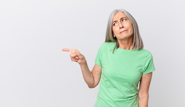 중년의 백발 여성은 슬프거나 화가 나거나 화가 나서 옆을 보고 옆을 가리키고 있다