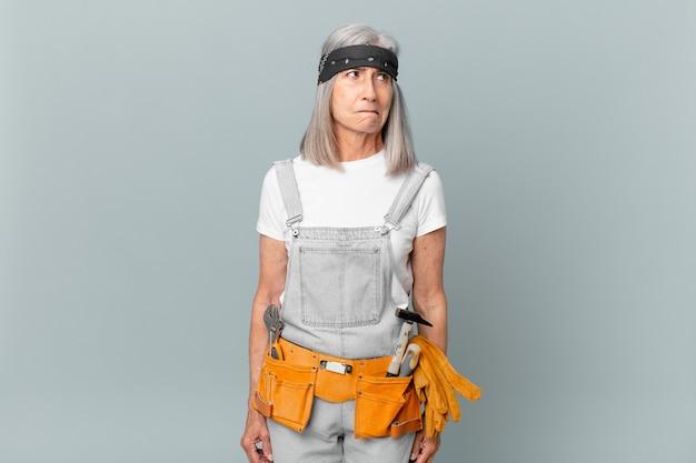 중년의 백발 여성은 슬프고 화가 나고 화가 나서 옆을 바라보며 작업복과 도구를 입고 있습니다. 가사 개념