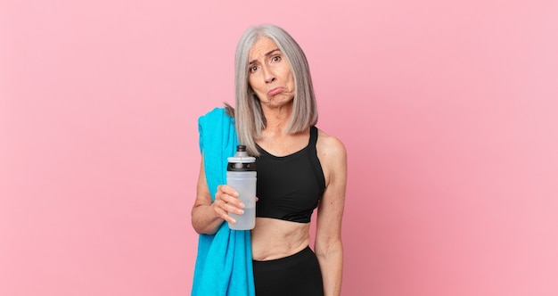 Middle age white hair woman feeling sad and whiney with an unhappy look and crying with a towel and water bottle. fitness concept