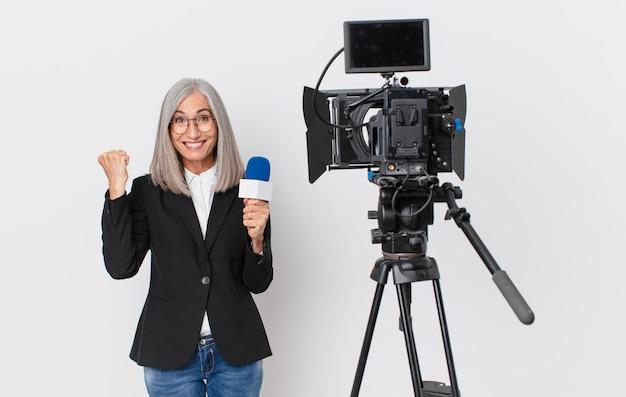 Женщина средних лет с белыми волосами чувствует себя потрясенной, смеется и празднует успех и держит микрофон. концепция телеведущего