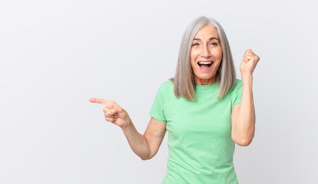 中年の白髪の女性はショックを受け、笑い、成功を祝い、側を指しています