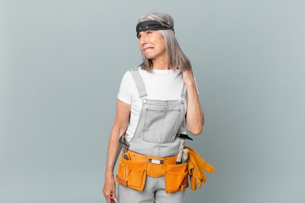 Женщина средних лет с белыми волосами чувствует стресс, тревогу, усталость и разочарование, носит рабочую одежду и инструменты. концепция домашнего хозяйства