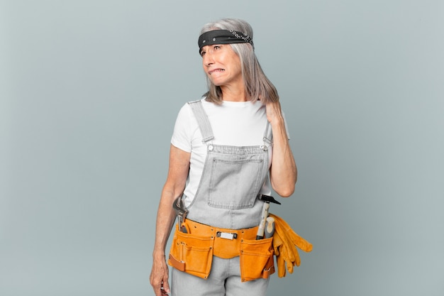 Middle age white hair woman feeling stressed, anxious, tired and frustrated and wearing work wear and tools. housekeeping concept