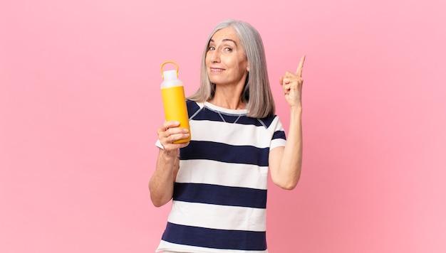 コーヒー魔法瓶を保持している中年の白髪の女性