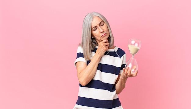Женщина среднего возраста с белыми волосами держит таймер с песочными часами