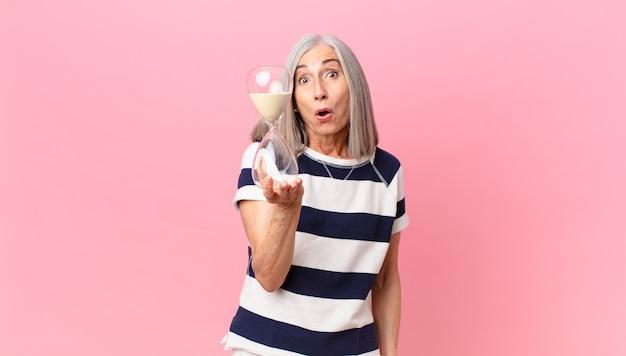 Женщина среднего возраста с белыми волосами, держащая таймер песочные часы