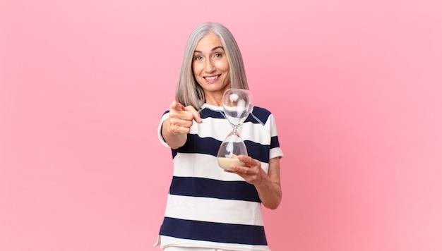 Среднего возраста женщина с белыми волосами держит таймер песочные часы