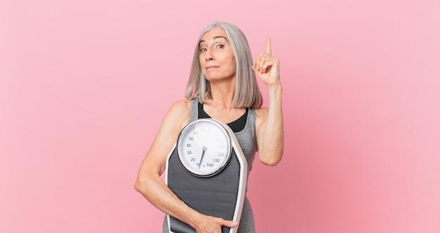 Женщина белых волос среднего возраста, держащая весы. фитнес и диета концепция
