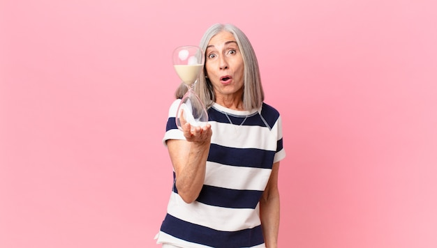 Middle age white hair woman holding a sandglass timer