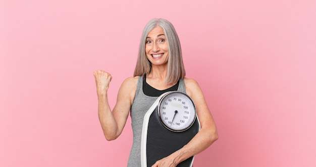 Middle age white hair woman holding a weight scale. fitness and diet concept