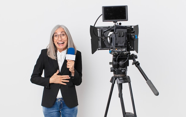 Женщина средних лет с белыми волосами громко смеется над какой-то веселой шуткой и держит микрофон. концепция телеведущего