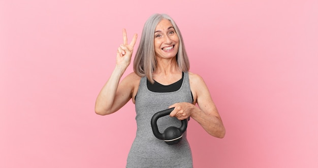 Middle age white hair woman lifting a dumbbell. fitness concept