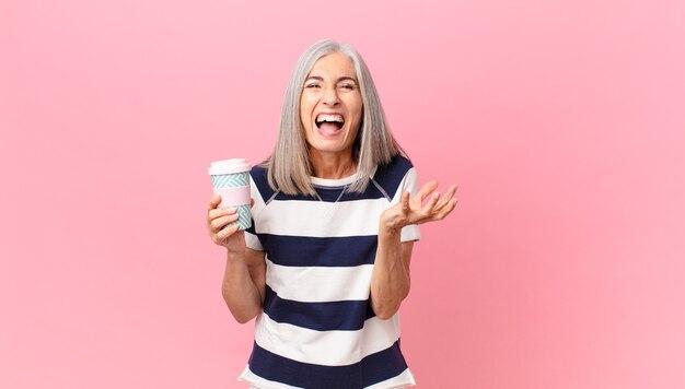 화가 나서 짜증이 나고 좌절감을 느끼고 커피 용기를 들고 중년 백발 여성
