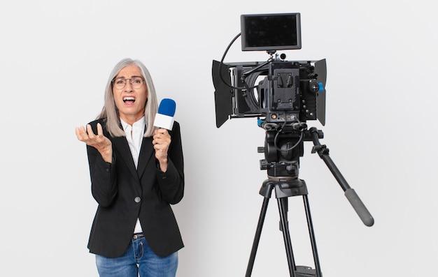 Женщина средних лет с белыми волосами выглядит отчаянно, разочарованно и подчеркнуто и держит микрофон. концепция телеведущего
